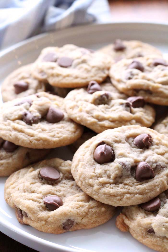 Perfect Chocolate Chip cookies on a white plate with a hand towel that has white and blue stripes in the background. There are about 10 cookies on the plate.
