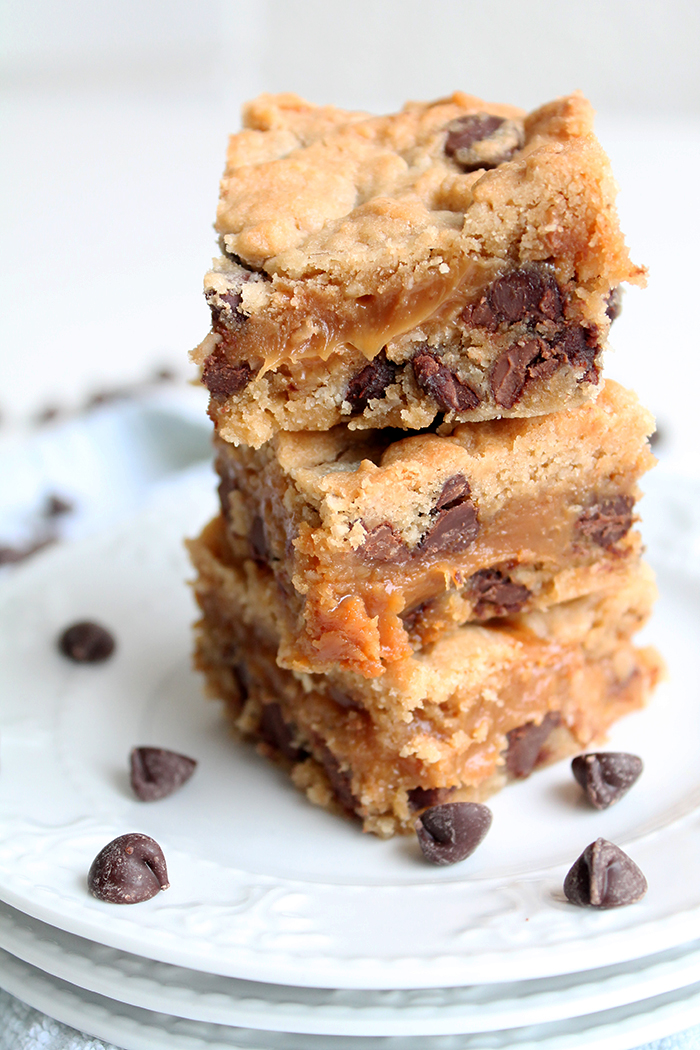 three cookie bars staked on top of each other with chocoalte chips scattered around them. The bars are stuffed with peanut butter caramel