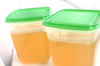 Two containers of chicken stock. They are plastic with green lids