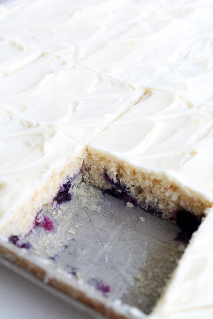 White sheet cake with lemon and blueberries in it and frosted with a creamy lemon frosting. Lemons in the background