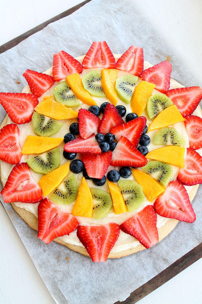 fruit pizza on parchment paper. Ariel shot so you can see the whole thing. Beautifully decorated with strawberries, mango, kiwi, and blueberries