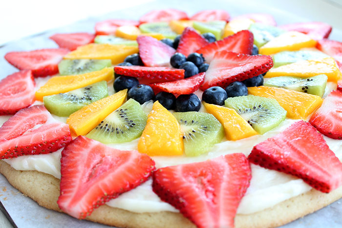 Fruit Pizza, Large sugar cookie with white frosting and fruit on top. You can only see half of it in the picture and the fruit is arranged in a pretty pattern. Very colorful.