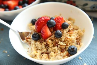 White Bowl with baked oatmeal and a splash of milk a fresh strawberries and blueberries