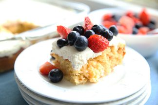 Tres Leches Cake on a white plate with whipped cream and berries