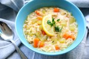 Soup with chicken, carrots, orzo pasta with a lemon wedge and parsley garnish in a blue bowl on a grey table cloth