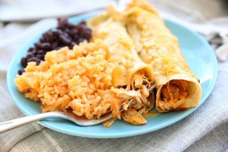 Blue plate with spanish rice, black beans and two chicken enchiladas