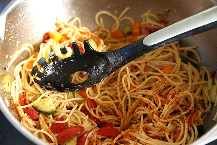 Large metal mixing bowl with spaghetti noodles, cucumber, tomatoes, bell pepper, red onion, olives and salami tossed together with italian salad dressing and sprinkles with salad supreme. there is a pasta spoon in the middle of it that was used to toss the salad