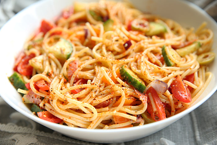 A bowl of spaghetti noodles mixed with veggies and italian salad dressing with salad supreme spice tossed together to make a pasta salad. It is in a white bowl.