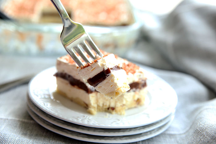 a piece of a four layer chocolate lasagna with a shortbread crust sitting on a stack of three small white plates. a fork is taking a bite off of the square of dessert. You can see the rest of the pan of dessert in the background.