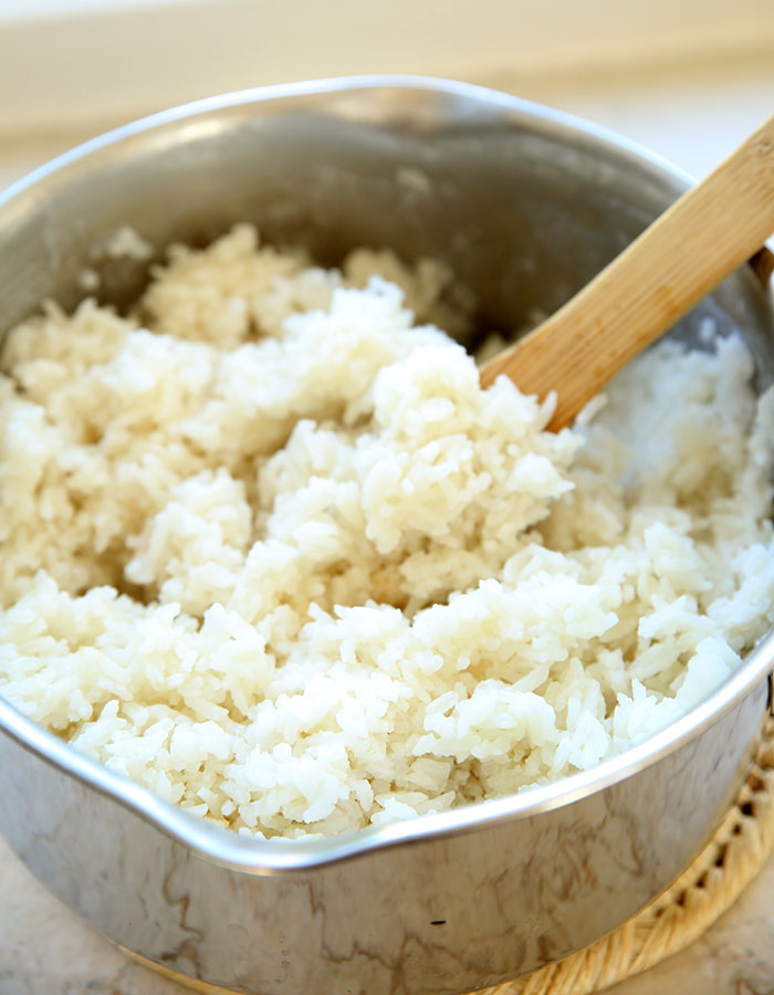 Coconut rice in a stainless steal sauce pan with a wooden spoon fluffing it.
