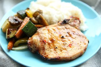 Blue plate with a grilled sweet chili pork chop on it and coconut rice and grilled veggies on the side