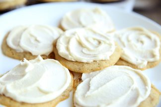 white plate full of fluffy banana cookies with white buttercream frosting