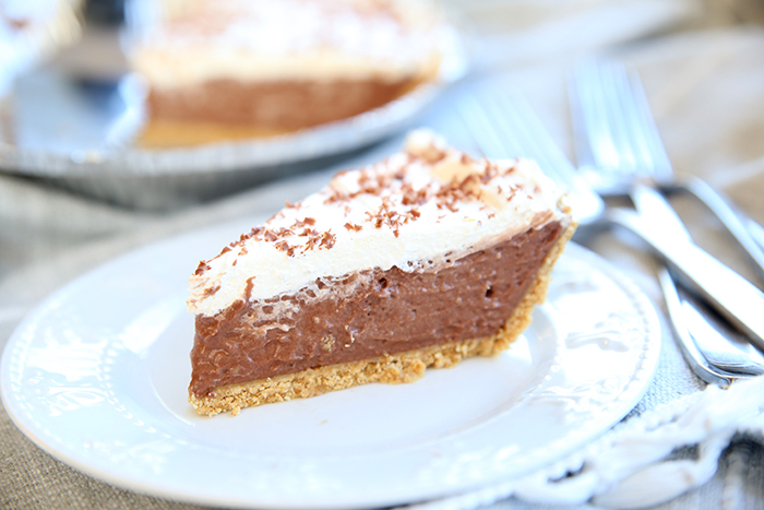 a perfect slice of french silk pie on a small white plate. You can see the rest of the pie in the background