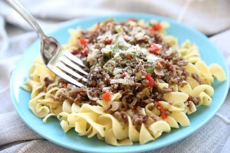 a small blue plate with beef and peppers served over egg noodles. It is sprinkled with Parmesan cheese. There is a fork taking a bite out