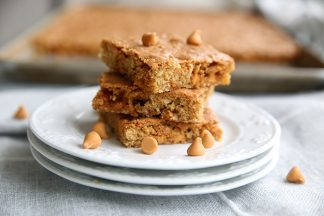 Stack of three Oatmeal Scotchie Bars on a stack of three plates, you can see the cookie sheet with the rest of the bars in the background