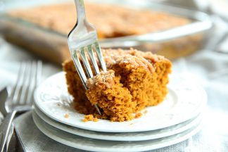 A piece of Pumpkin Coffee Cake with a fork on three stacked small white plates with the rest of the cake in a pan in the background.