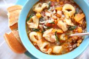 Blue bowl with sausage tortellini soup with sweet potatoes. A spoon is in the bowl and bread on the side.