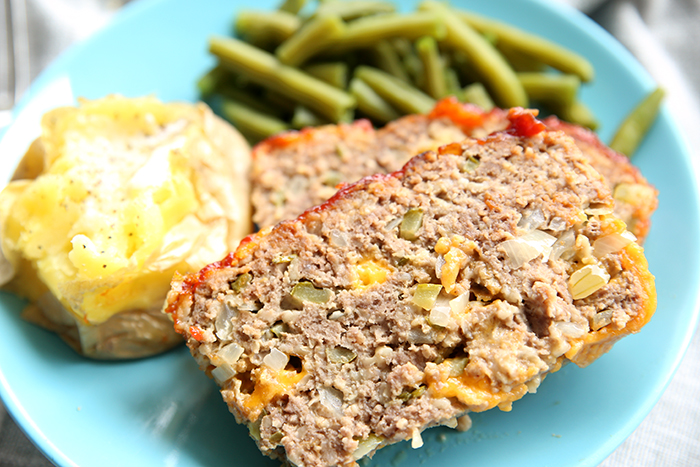 Two slices of Cheeseburger Meatloaf with green beans and a baked potato all sitting on a blue plate