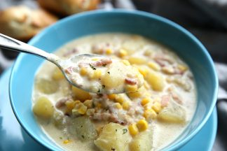 A blue bowl full of corn chowder. You can see potatoes, corn, bacon and onions in the creamy broth
