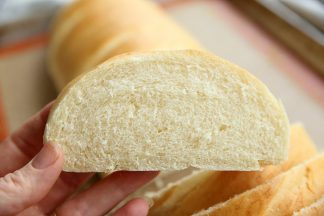 A hand holding a slice of french bread, you can see the rest of the loaf in the background.