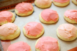 a sheet pan covered with a silpat. the cookie sheet also has a dozen old fashioned sour cream drop cookies on it. the cookies are frosted with pink frosting.