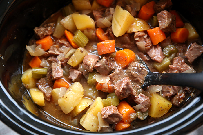 A partial picture of a black crock pot with beef stew in it. A ladle spoon is dipped in the stew at the top ready to scoop into a bowl.