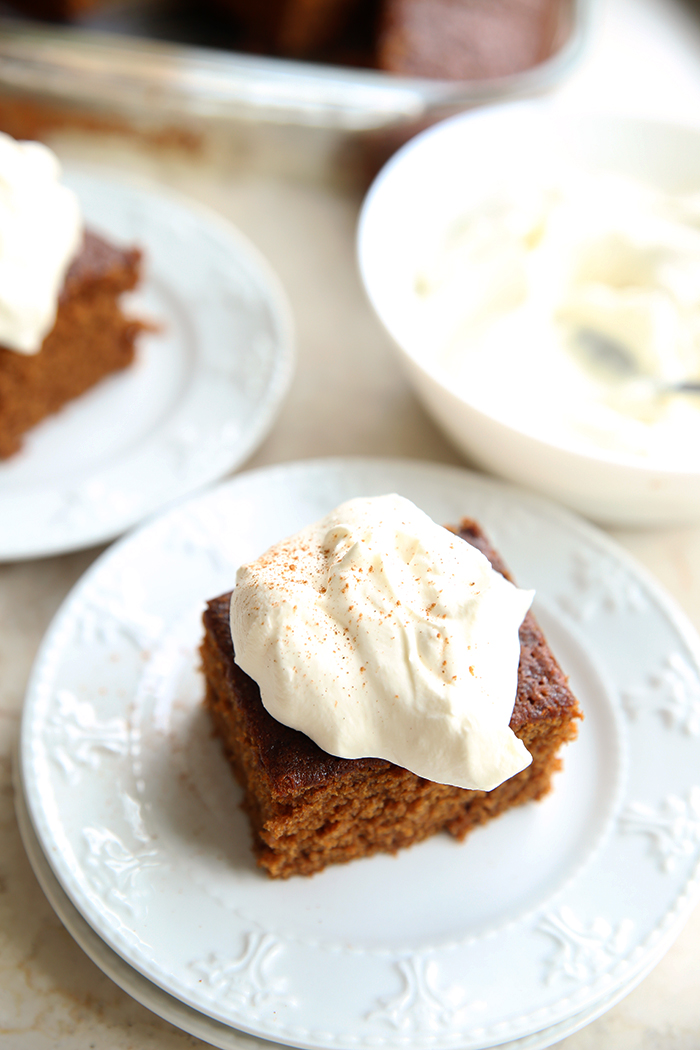 White plate with a piece of gingerbread cake, topped with whipping cream. In the background, you can see another white plate with a piece of cake and a white bowl with whipping cream