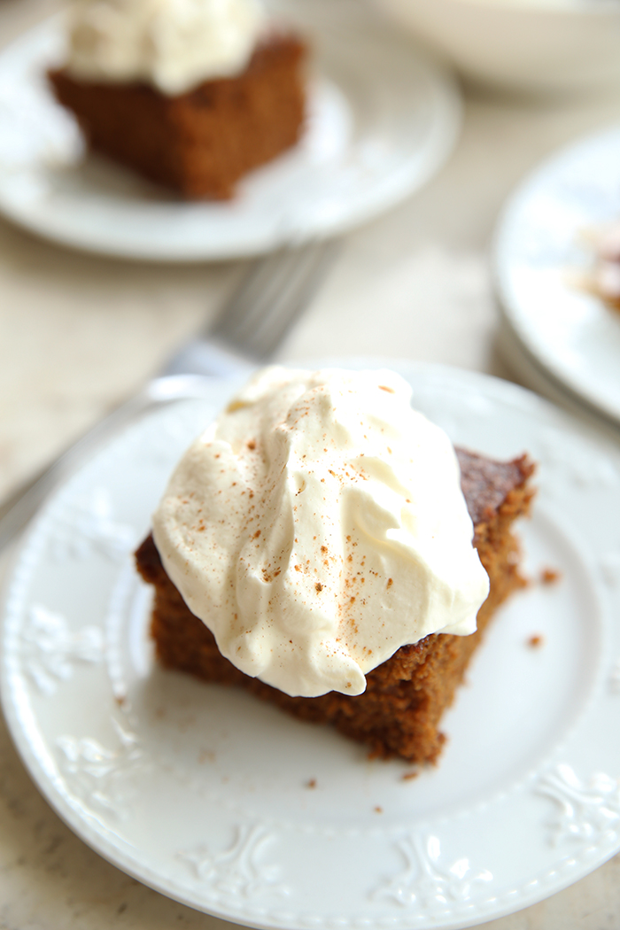 White plate with a piece of gingerbread cake, topped with whipping cream. In the background, you can see more white plates with a piece of cake.