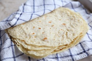 Homemade flour tortillas wrapped in a hand towel that is blue and white plaid.