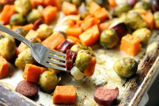 Sheet pan of brussel sprouts, sweet potatoes and Kielbasa with a fork taking some of the food off the sheet pan