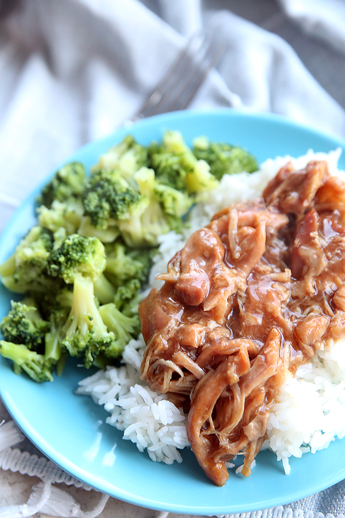 Slow Cooker Teriyaki Chicken served on a blue plate with rice and broccoli