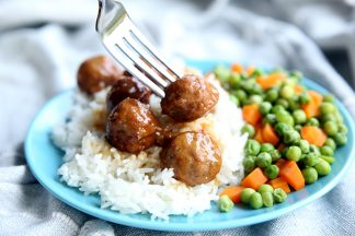 A blue plate sitting on top of a table cloth with peas and carrots and teriyaki meatballs topped on jasmine rice with a fork in a meatball