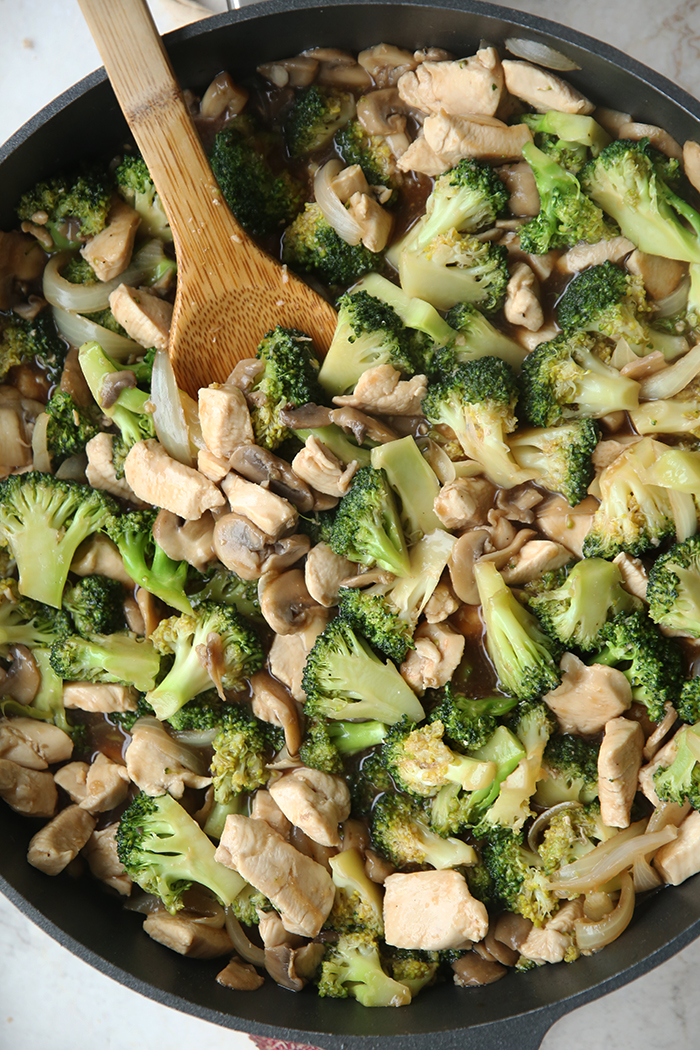 A vertical photo of broccoli chicken stir fry in a large skillet with a wooden stirring spoon at the top sticking partway out of the stir fry.