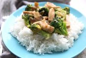 A fork is on the left side of a blue plate, sitting on a grey napkin. The blue plate has white rice on it topped with the broccoli chicken stir fry.