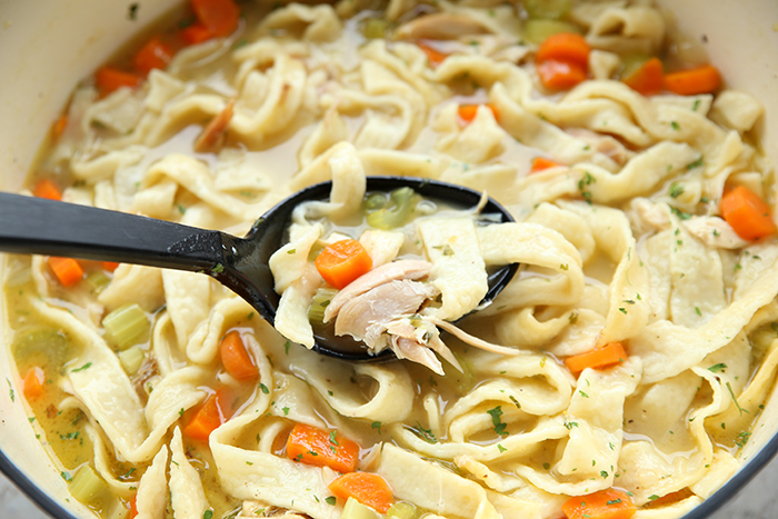 homemade chicken noodle soup in a pot with a ladle taking out a big scoop of soup. You can see carrots, celery and chicken in the soup along with the homemade noodles.