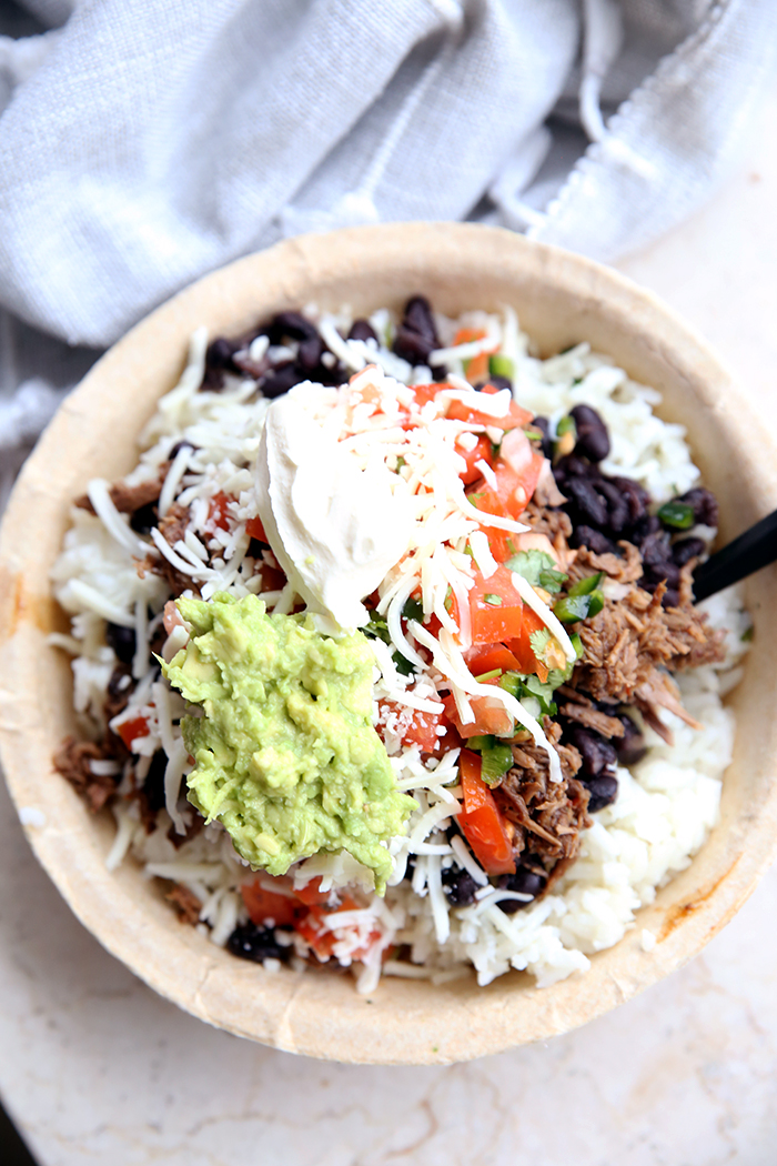Chipotle Beef in a paper bowl with white rice, pico de Gallo, black beans, sour cream, shredded cheese and guacamole with a black plastic spoon inserted in the right side of the dish. Above the paper bowl is a grey cloth napkin.
