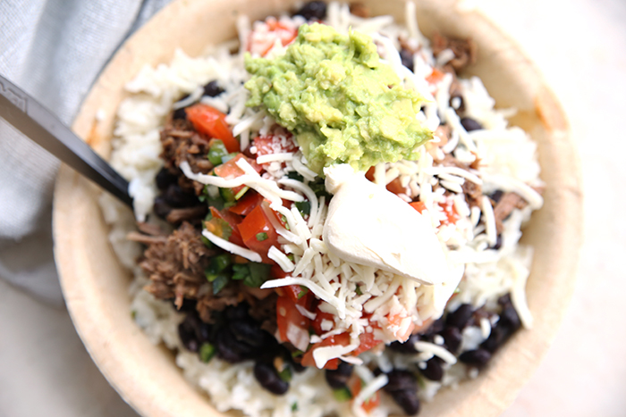 Beef Barbacoa topped on white rice with black beans, pico de Gallo, shredded white cheese, guacamole and sour cream on top of the beef, all in a paper bowl with a black plastic spoon inserted into the dish on the left side. There's a partial picture of a grey cloth napkin in the upper left corner.