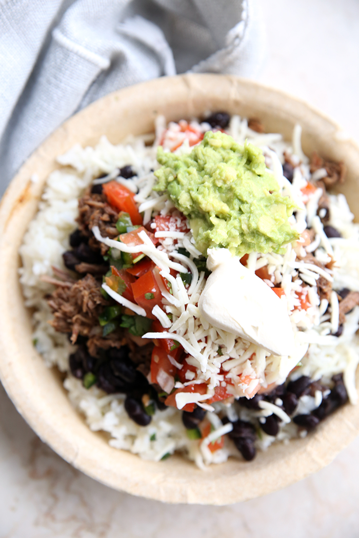 A paper bowl filled with rice topped with Chipotle Beef Barbacoa, black beans, pico de Gallo, shredded cheese, guacamole, and sour cream. In the upper right corner is a partial picture of a grey cloth napkin