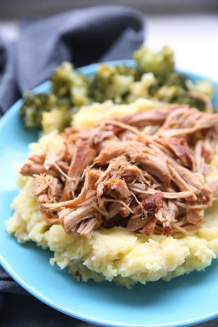 A blue plate holding a serving of crazy good pork and potatoes with green beans