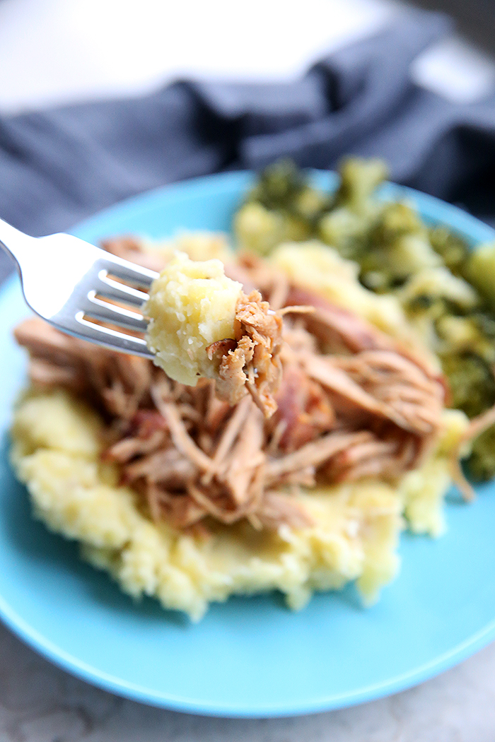 A blue plate holding a serving of crazy good pork and potatoes with green beans and a fork with a bite of the food ready to be eaten