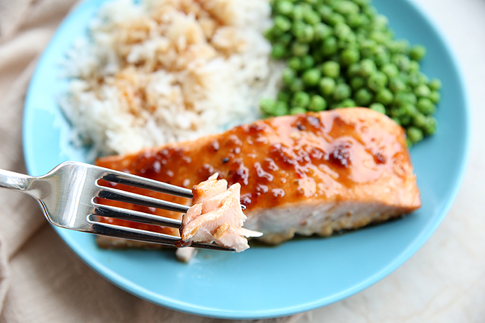 A blue plate with a teriyaki salmon filet, coconut rice and peas with cloth tan napkin in the background on the left and a fork held above the salmon with a piece of salmon on it.