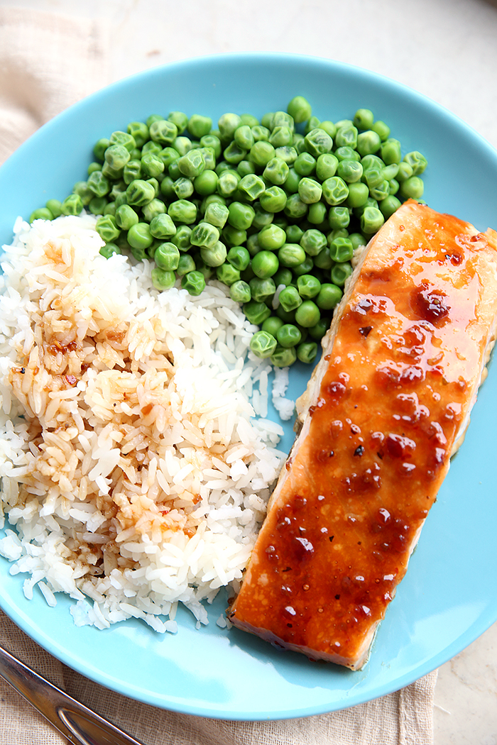 A piece of teriyaki salmon siting on a blue plate with coconut rice topped with teriyaki sauce and green peas on the side.
