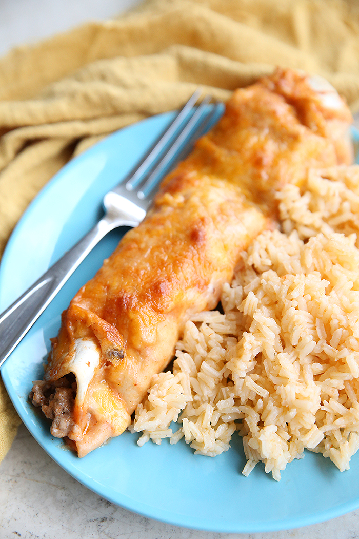 A ground beef enchilada, Spanish Rice, and a fork all sitting on a light blue plate with a yellow dish cloth lying above the plate.