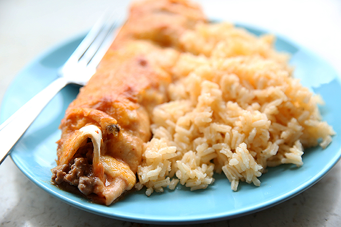 A blue plate topped with one enchilada, a fork and Spanish Rice.