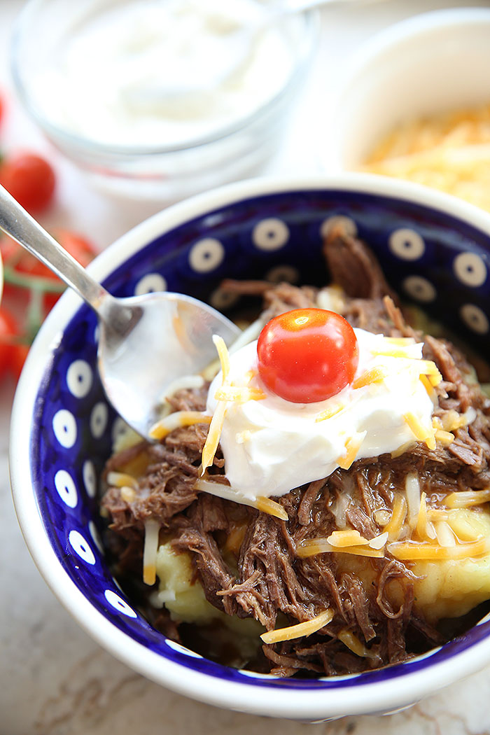 A serving of Instant Pot Beef Sundaes in a blue bowl with a spoon digging in to take a bite.