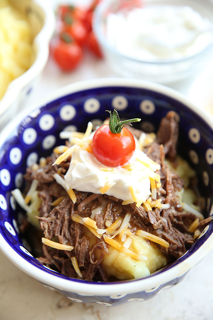 A Polish pottery peacock patterned bowl with mashed potatoes on the bottom topped with roast beef gravy, a dollop of sour cream, shredded cheese and a cherry tomato on top. In the background is a small glass bowl of sour cream, a few cherry tomatoes, and a partial picture of a serving bowl of mashed potatoes.
