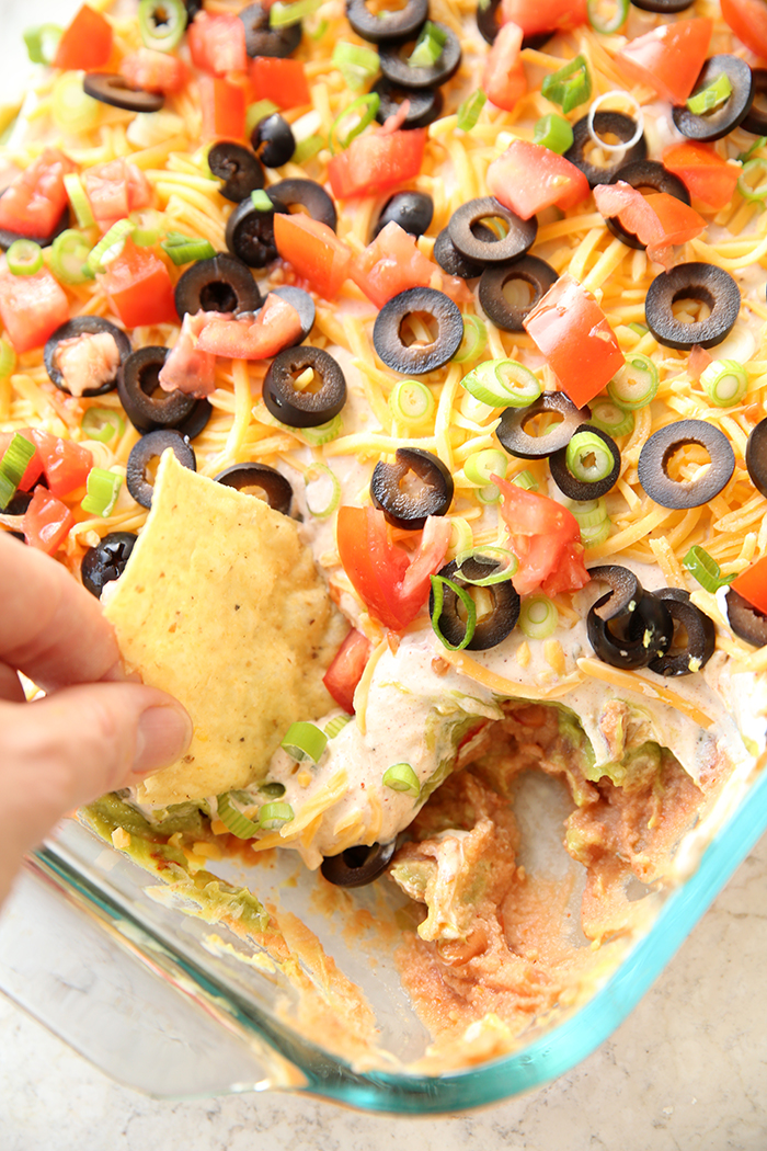 A glass pan holding Ultimate Seven Layer dip with a chip being dipped into the corner
