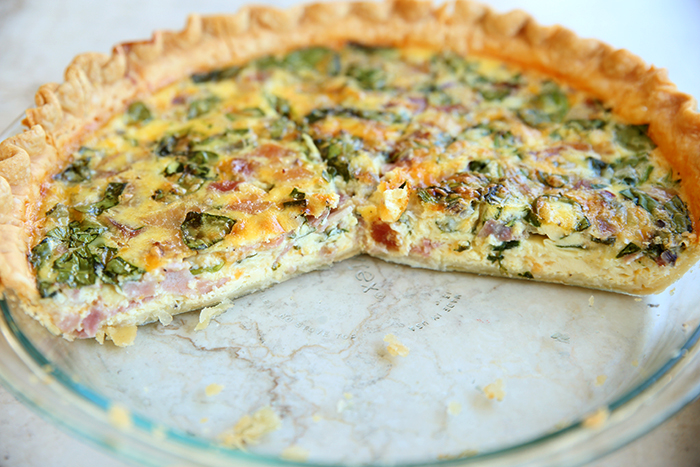 A glass pie dish of quiche with several pieces cut out.